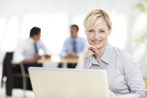 Pretty businesswoman smiling confidently at you while working on her laptop at her desk - copyspace