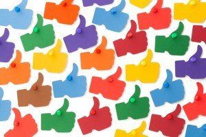 Colourful I LIKE thumbs up pinned to white surface